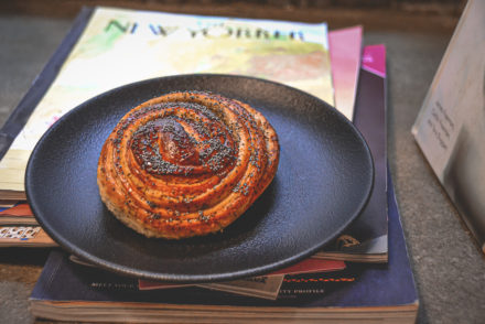 Marzipan poppyseed bun on a plate above magazines